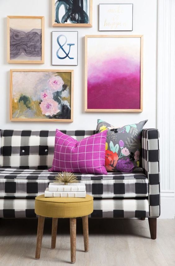 a black and white buffalo check sofa is brightened up with a lot of colorful artworks over it