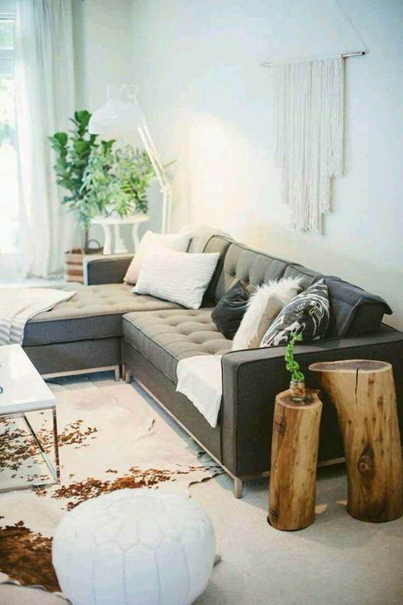 a boho chic space with a large grey secctional sofa that makes the base of the room