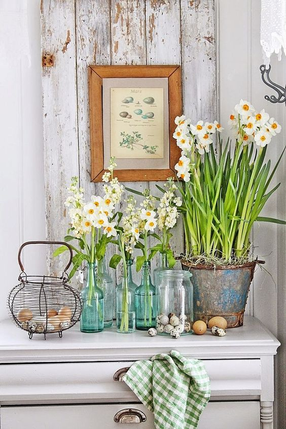 a console styled with fresh blooms in clear vases and a bucket, a nest with real eggs