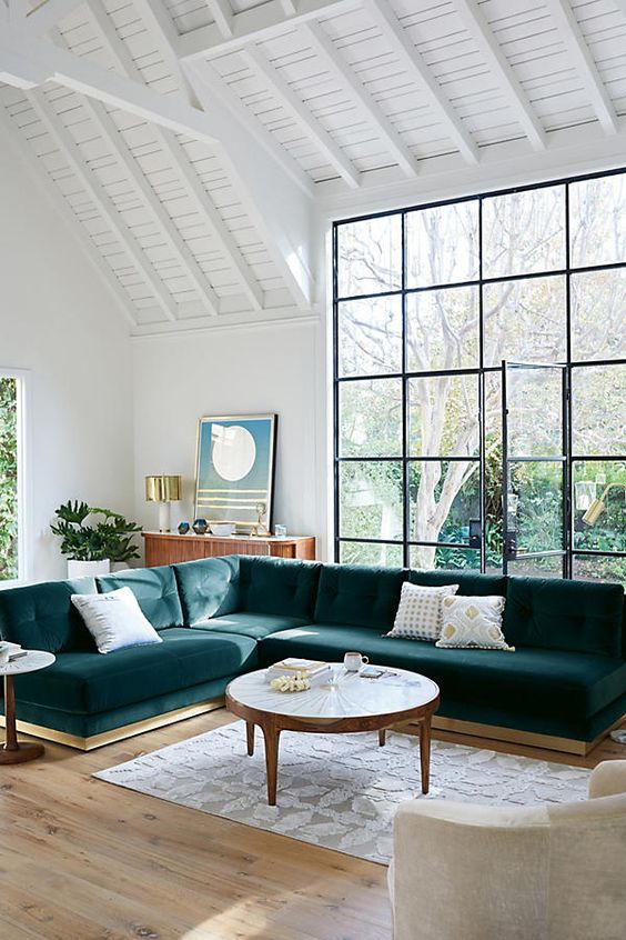 a large teal velvet L-shaped sectional sofa is a statement piece in this airy space