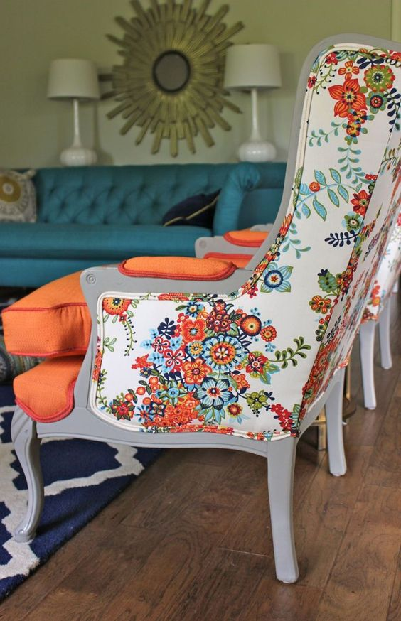 a vintage wingback armchair is given a bold look with floral upholstery on the back and orange on the front