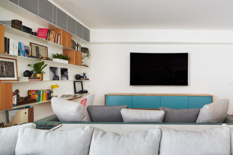 The living space is done with comfy grey sofas and a gorgeous wall unit that consists of thin open shelves