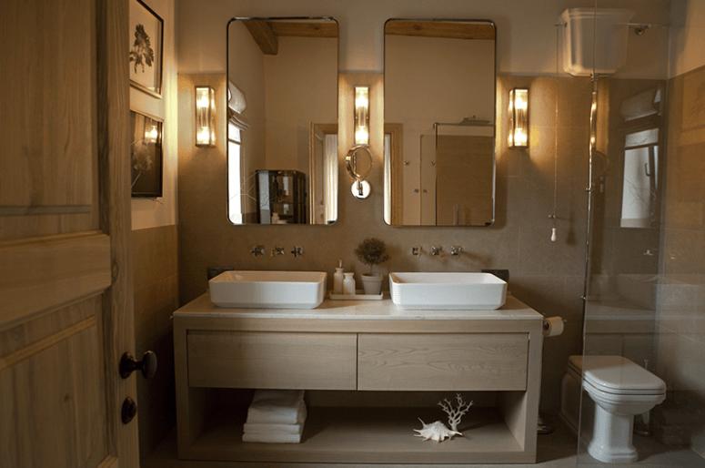 The master bathroom is clad with light-colored tiles and wooden vanity, there's a shower and a double sink