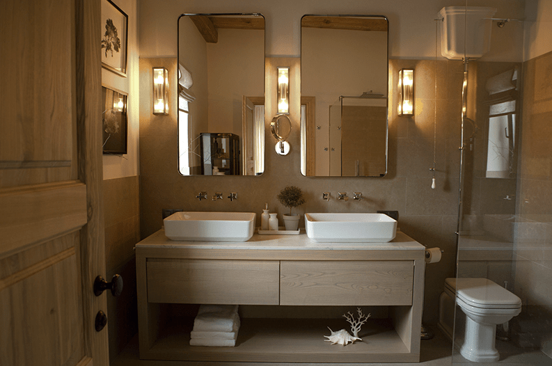 The master bathroom is clad with light colored tiles and wooden vanity, there's a shower and a double sink