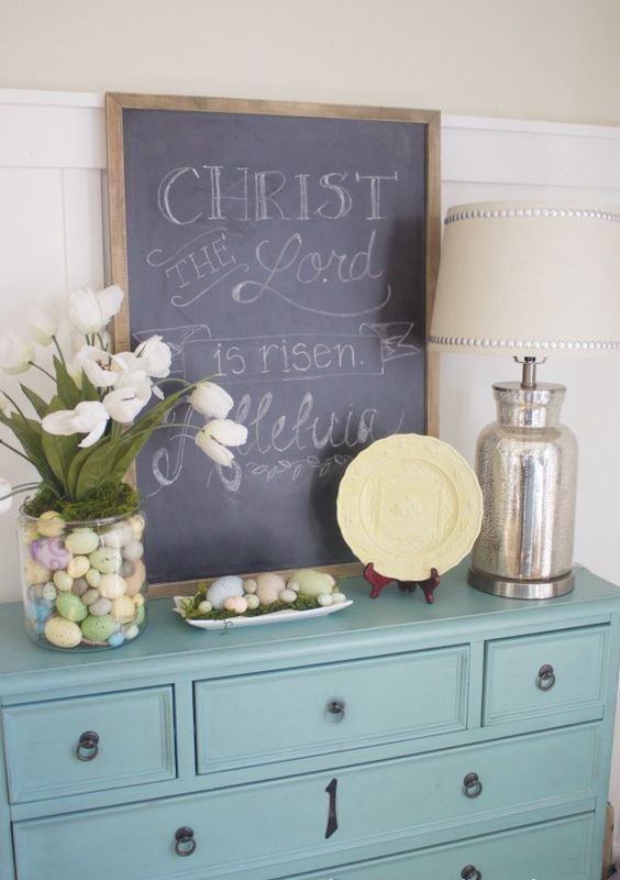 a chalkboard sign, pastel eggs in the tray and a large glass pot with moss, pastel eggs and white tulips
