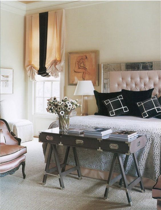 a chic bedroom accomodates not only a large bed but also a vintage chair and a gorgeous trestle desk at the foot of the bed