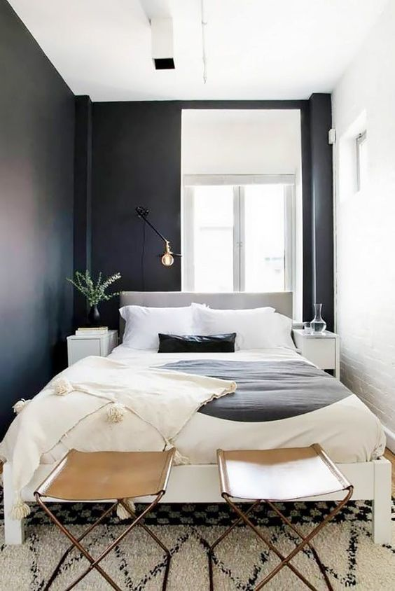 a small bedroom with a large bed and black and white walls looks bigger than it could