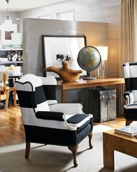 a traditional wingback chair in black and white stripes for a vintage and rustic interior