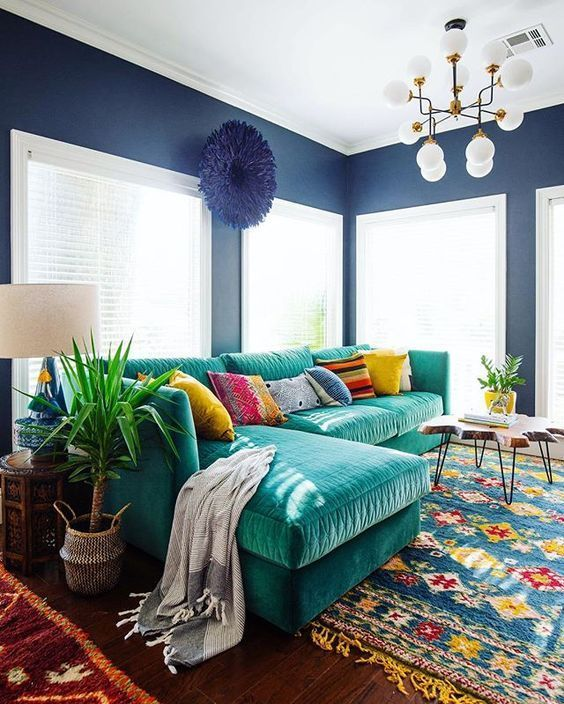 an L shaped emerald velvet sofa with colorful pillows is the main eye catcher that adds color to the space