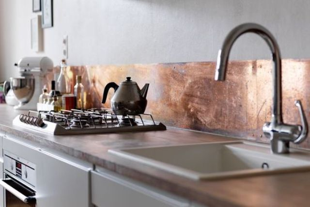 shiny copper metal backsplash adds eye-catchiness to the kitchen and a cool feel