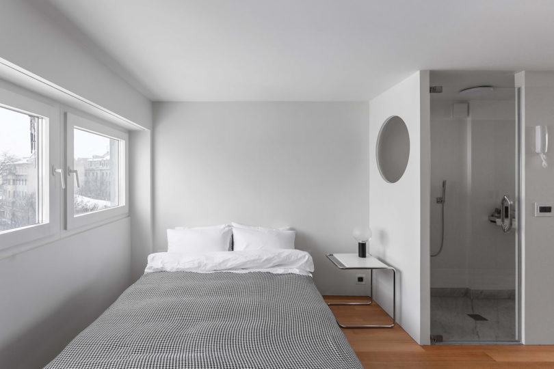 The bedroom space is serene and small, with a large bed and a single nightstand