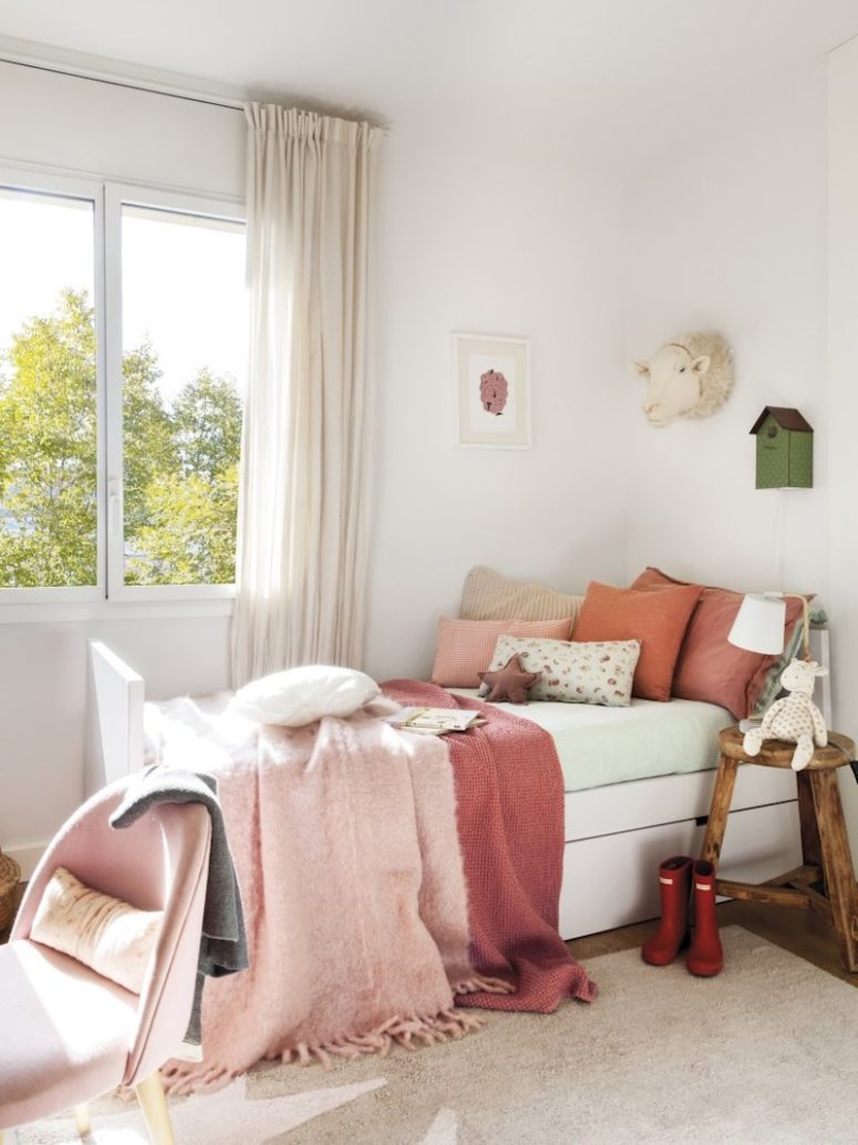 The girls' bedroom is done in red and pinks, with layered textiles and some rustic touches