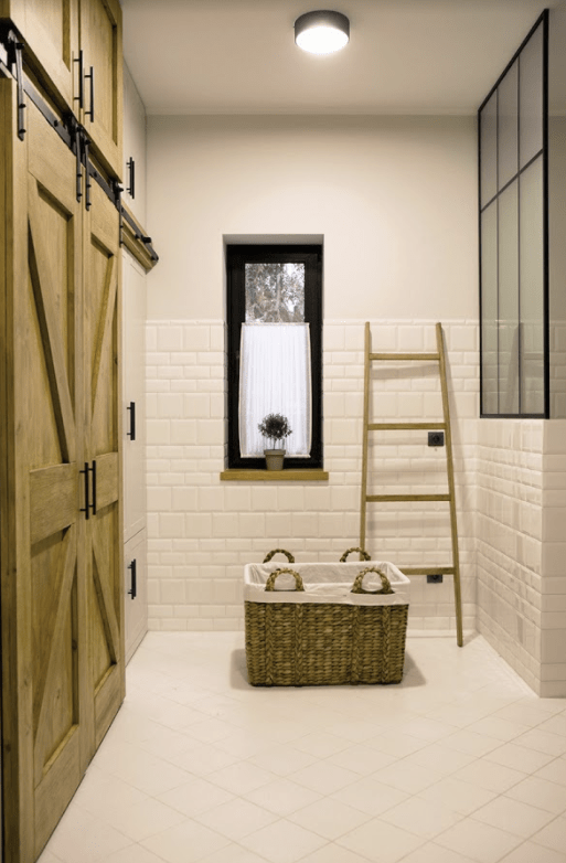The second bathroom is clad with white tiles, there's a vintage-looking shower with glazing and tiles