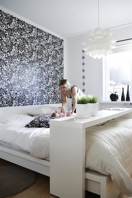 a modern bedroom with a printed headboard wall and a comfy bench and caddy for functionality