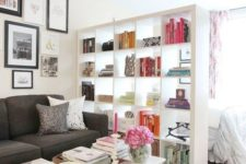 10 a modern white shelving unit divides a living room and a sleeping space