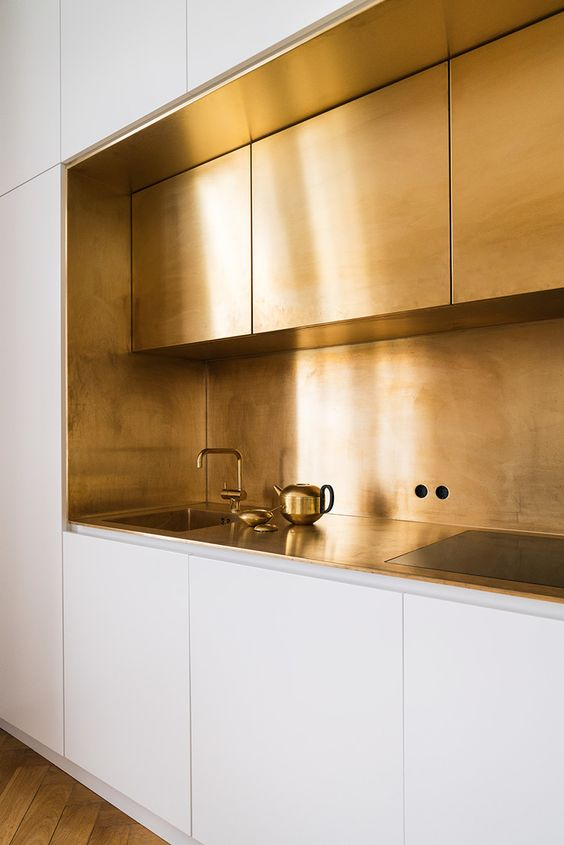 a polished gold kitchen backsplash and upper cabinets create a glam minimalist look in the white kitchen