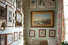10 a small vintage bathroom is given a living room feel with lots of artworks and sconces