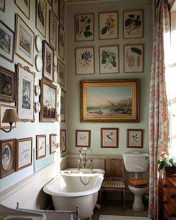 a small vintage bathroom is given a living room feel with lots of artworks and sconces
