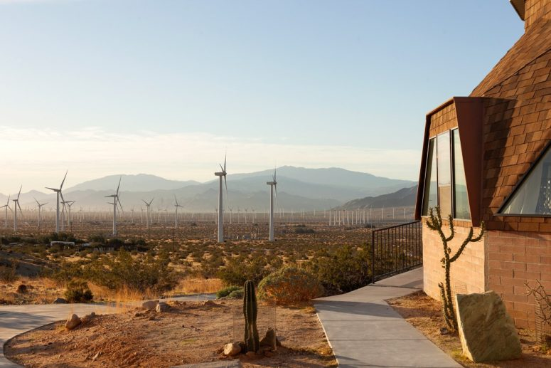 The outdoor spaces feature wind turbines and a typical desert landscape