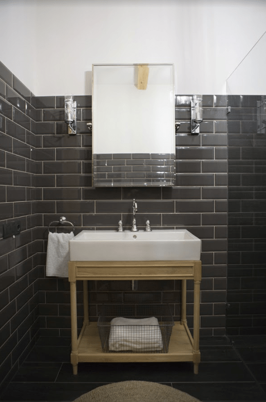 The powder room is clad with graphite grey tiles accented with white grout