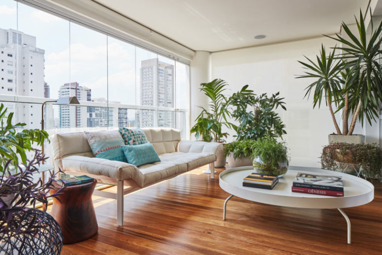 The terrace sitting space is done with a modern sofa, potted plants and greenery and a glazed wall that shows off a city landscape