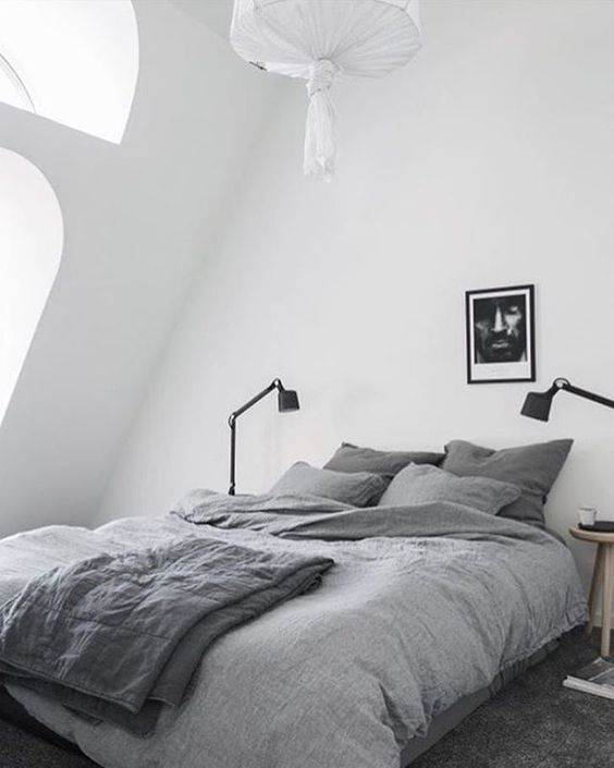 a comfy and small Scandinavian attic bedroom with a grey bed and some lamps - nothing else is needed here