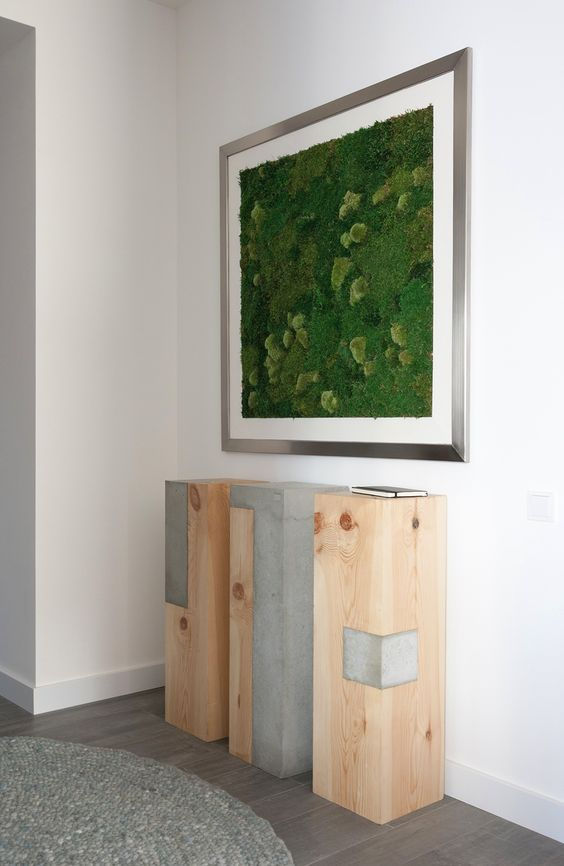 a framed moss wall art over an industrial three piece console is a bold modern idea