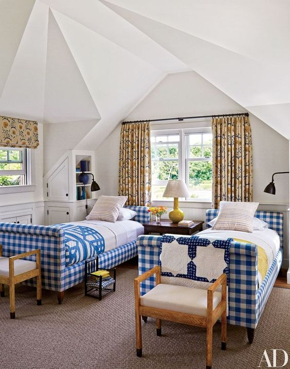 a guest bedroom done with blue and white buffalo check upholstered beds to bring a welcoming feel