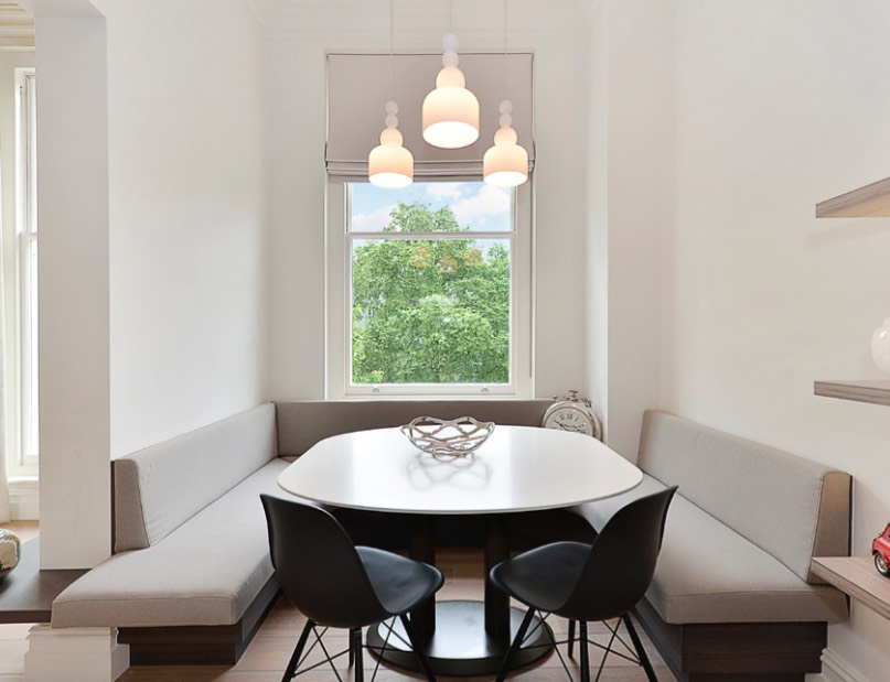 a tiny dining space features built in banquettes and a rounded table that don't make the space feel small