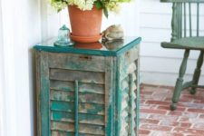 11 an outdoor side table of old shutters and a couple of wooden planks, the aged look fo the shutters is highlighted