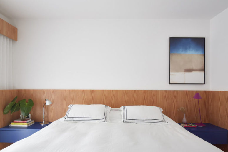 The master bedroom is done in white, light-colored wood and with blue touches