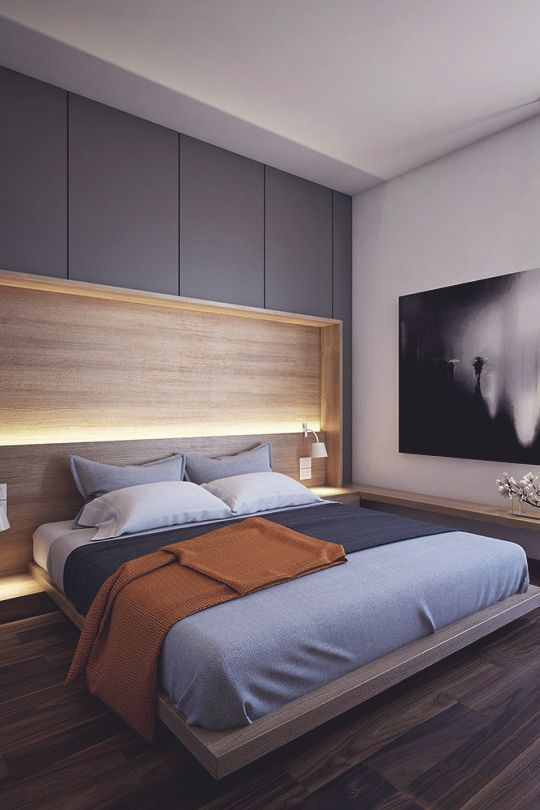 a contemporary bedroom with a floating bed, a lit up headboard and a large artwork