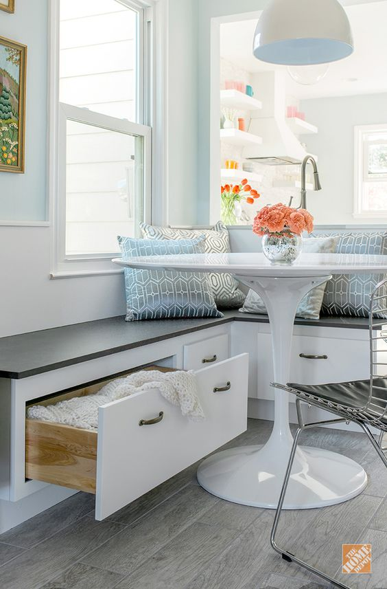 a cozy breakfast nook with a built in corner bench with storage is a perfect solution