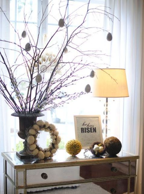 a mirrored console with an egg wreath, an Easter tree with egg ornaments and moss balls and a nest