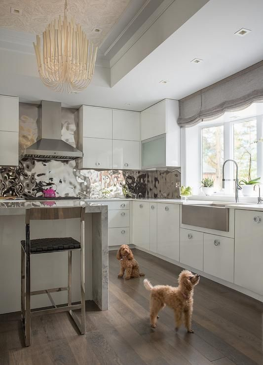 a polished hammered metal backsplash adds a glam feel to the white and grey kitchen