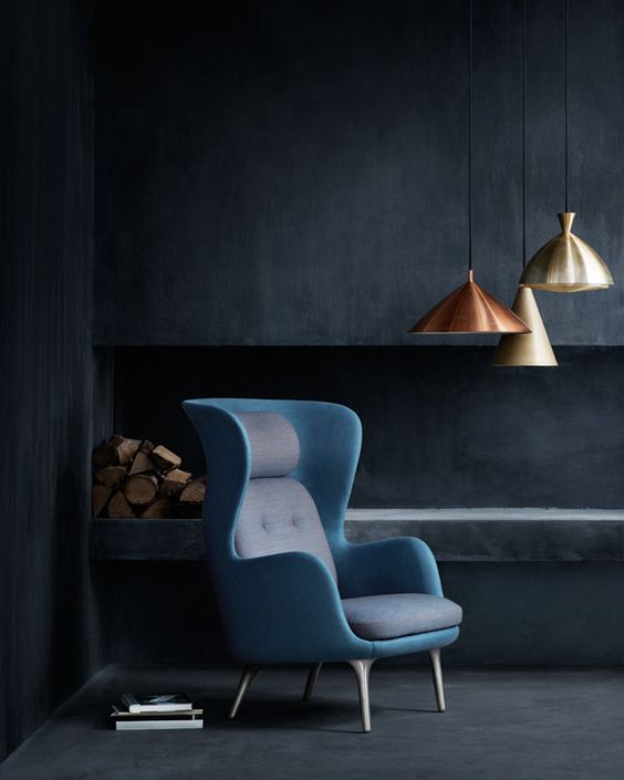 a bold wingback chair with a mid-century modern twist in grey and blue is a show-stopper in this moody space