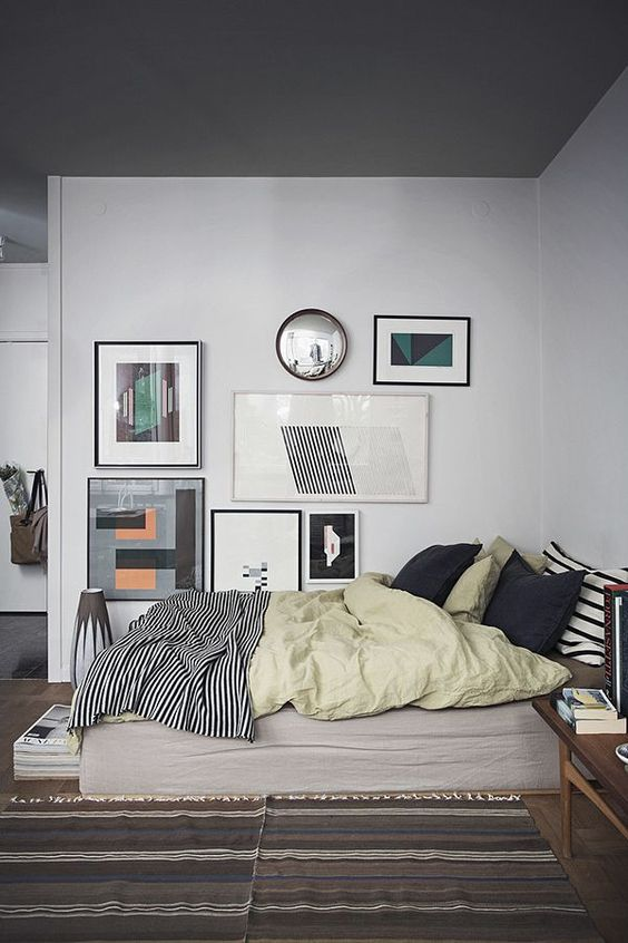 a large and bold asymmetrical gallery wall is a great accent feature for the bedroom