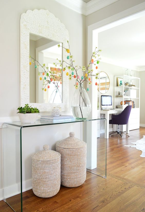 a modern acrylic console with potted succulents and an Easter tree with colorful egg ornaments