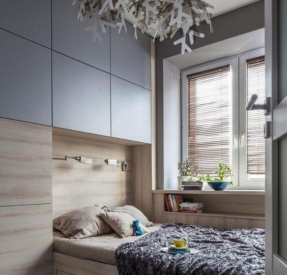 a small bedroom with built-in storage and a built-in bed with increased functionality
