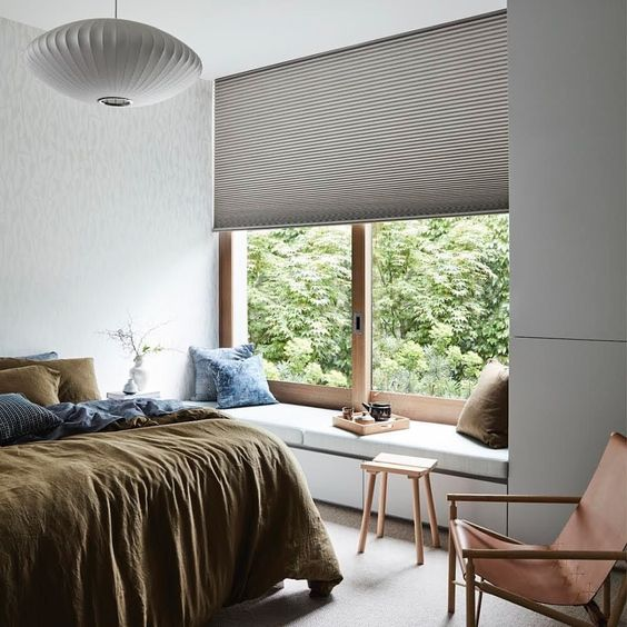 a textural Roman shade adds interest to the bedroom while keeping it private enough