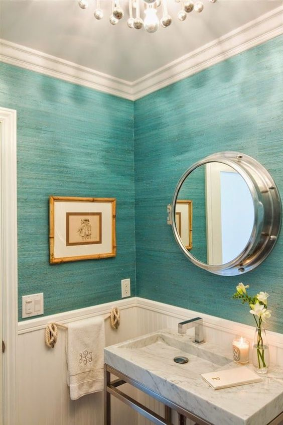 an ocean-inspired bathroom with wainscoting that protects the wallpaper and makes the bathroom feel vintage