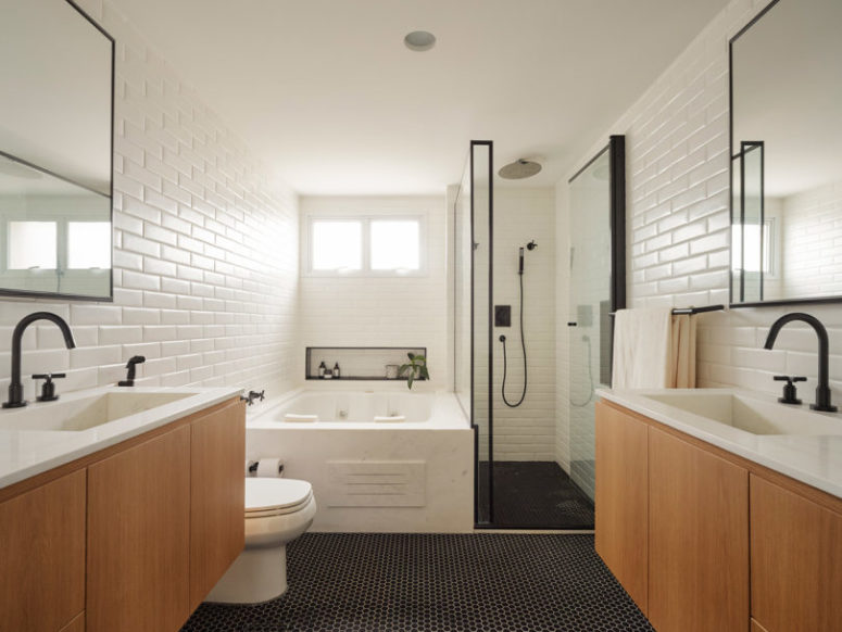 The master bathroom is done with white tiles, black penny ones on the floor and light-colored wood