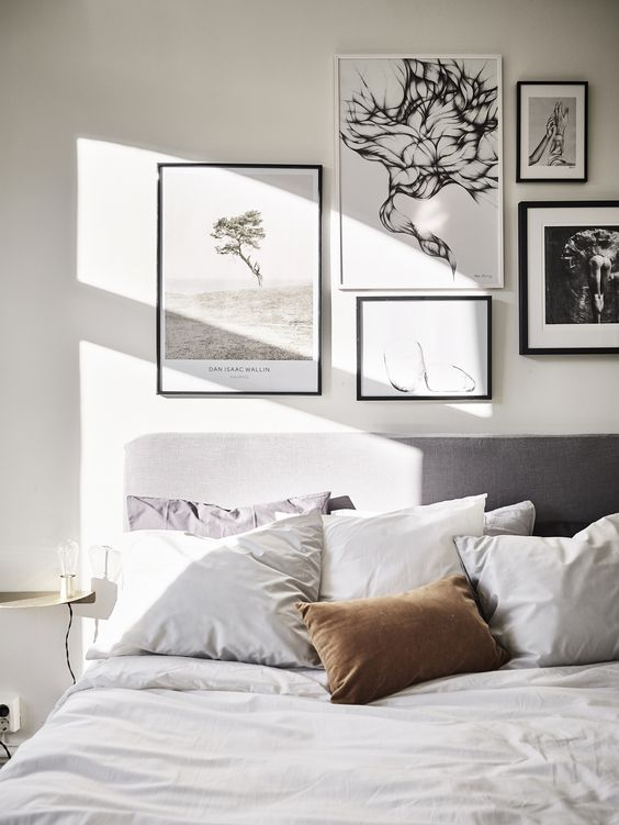 a black and white gallery wall with photos is a great option for a contemporary bedroom