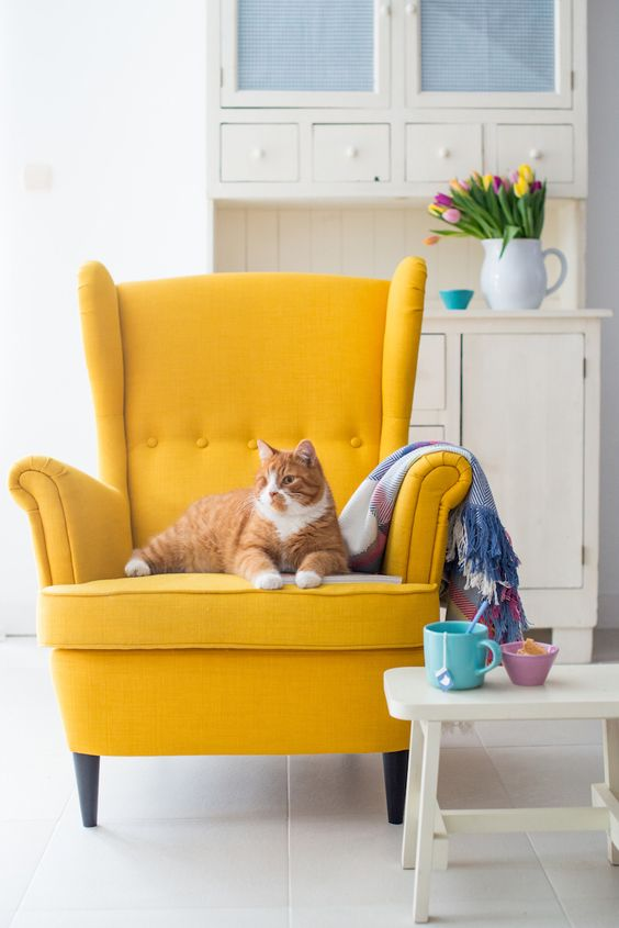 a bold yellow wingback brings a cheerful feel and colorful touch to the space