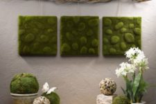 14 a moss wall art trio and a couple of balls create a fresh spring feeling in the space