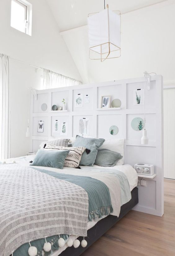 a pony wall with shelves and artworks as a decorative element and a divider for the sleeping and dressing space