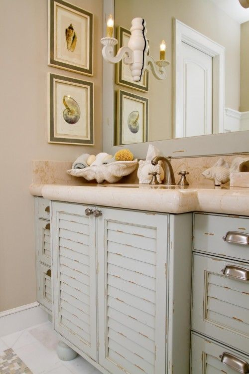 a sink vanity made of old pastel-colored shutters and a stone countertop for a beach-inspired bathroom
