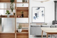 14 a wooden shelving unit with glass parts to separate the dining and living rooms