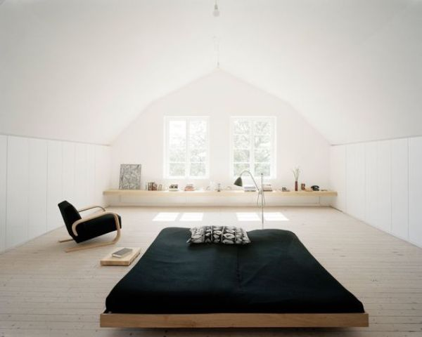 an airy minimalist attic bedroom with a bed in the center, a windowsill shelf and a chair