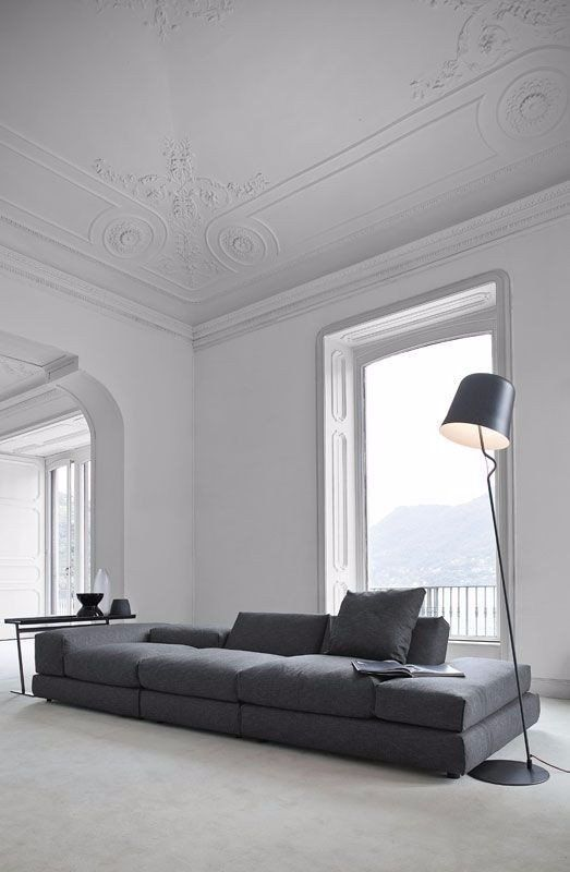 the whole large space is done in white, with a dark grey sofa and lamp, with lots of no decor space